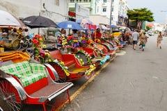 Väntande på kund för Rickshawchaufför på den Georgetown gatan royaltyfria bilder