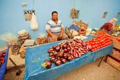 Väntande på kunder för lycklig grönsakaffärsman med aubergine och tomater på lantlig marknad i Turkiet Royaltyfri Bild