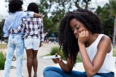 Väntande på meddelande för ensam afrikansk amerikankvinna royaltyfri fotografi