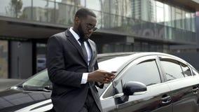 Väntande på partners för Rich Afro-American man nära kontorsbyggnad som gör affär royaltyfri foto