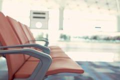 Väntande stolar av passagerare i röd flygplats Bakgrunden är atmosfären i flygplatsen För passagerare som väntar för att lämna, e royaltyfri fotografi