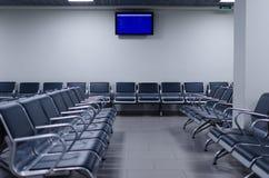 Väntande zon i en flygplats med stolar och schemat Royaltyfria Bilder