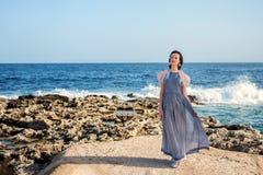 Värdig spenslig nymphet i långa moment för en klänning trevligt på lavakusten av ett blått rasa hav med vitt skum Arkivbild