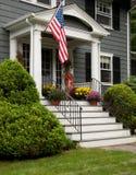 Värdigt hus med hängande över moment för flagga Arkivfoto