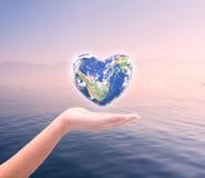 Värld i hjärtaform med over kvinnamänniskahänder Royaltyfri Bild