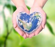 Värld i hjärtaform med over kvinnamänniskahänder Royaltyfria Bilder
