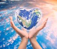Värld i hjärtaform med over kvinnamänniskahänder Arkivbilder