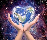 Värld i hjärtaform med over kvinnamänniskahänder Fotografering för Bildbyråer