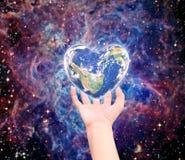 Värld i hjärtaform med over kvinnamänniskahänder Arkivfoton