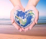 Värld i hjärtaform med over kvinnamänniskahänder Royaltyfri Foto