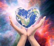 Värld i hjärtaform med over kvinnamänniskahänder Arkivbild