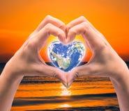 Värld i hjärtaform med over kvinnamänniskahänder Royaltyfri Fotografi