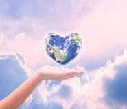 Värld i hjärtaform med over kvinnamänniskahänder på suddig natu Royaltyfria Bilder