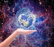 Värld i hjärtaform med over kvinnamänniskahänder på suddig natu Royaltyfri Foto