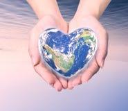 Värld i hjärtaform med over kvinnamänniskahänder på suddig natu Royaltyfria Foton