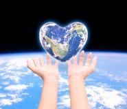 Värld i hjärtaform med over kvinnamänniskahänder på suddig natu Royaltyfri Fotografi