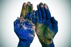 Världen i dina händer (jordöversikten som möbleras av NASA) Arkivbild