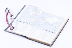 En boka med exponeringsglas och visar världstimezonen Royaltyfri Foto