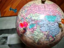 Världsjordklot med det färgrika stiftet kopiera avstånd Idéer och begreppsbruk arkivbild