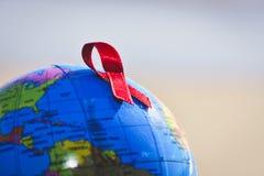 Världsjordklot med ett rött band för kampen mot HJÄLPMEDEL Royaltyfria Bilder