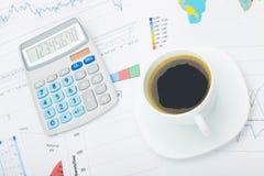 Världskarta och några finansiella diagram under den kaffekoppen och räknemaskinen Arkivfoto