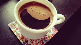 Världsleendena - le på på kaffe i en vit kopp på färgblocket på det svarta skrivbordet Royaltyfri Bild