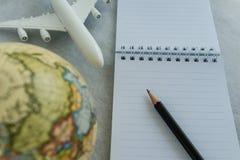 Världsloppbegrepp med blyertspennan på vitt anmärkningspapper, leksakairpla royaltyfria foton