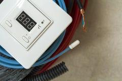 Värma golvsystemet binder, kablar och kontrollbordet Renovering- och konstruktionsbegrepp Komforthus arkivfoto