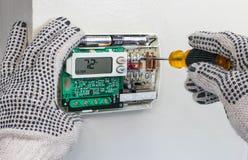 Värma upp i masugn repairmanen som installerar digital uppvärmning och kyler termostaten arkivbilder
