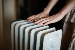 Värme av hans händer över ett element Varmt batteri royaltyfri bild