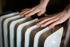 Värme av hans händer över ett element Varmt batteri fotografering för bildbyråer