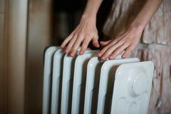 Värme av hans händer över ett element Varmt batteri royaltyfri fotografi