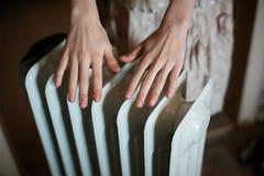 Värme av hans händer över ett element Varmt batteri arkivfoton
