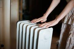 Värme av hans händer över ett element Varmt batteri arkivbild