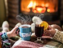 Värme och avslappnande near spis med en kopp av den varma drinken royaltyfri foto