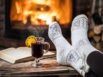 Värme och avslappnande near spis med en kopp av varmt vin arkivbild
