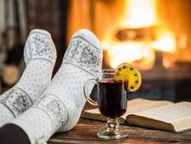 Värme och avslappnande near spis med en kopp av varmt vin och a arkivbild