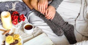 Värme och slags tvåsittssoffa, flickan i tröjan Royaltyfria Foton