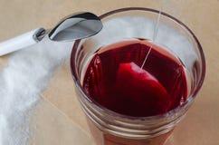 Värme rött te och tepåsen i exponeringsglas, på ljus bakgrund för brunt papper arkivbild