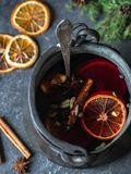 Värmealkoholdryck för traditionell vinter - funderat vin Varmt vin med frukter och kryddor i tappningmetallkastare på mörkt - grå arkivbilder
