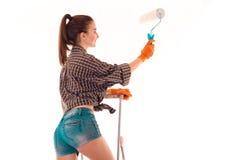 Värt roterande för ung sexig flicka tillbaka framåt med ett härligt behind och innehav en rulle för att måla isolerade väggar Arkivbild