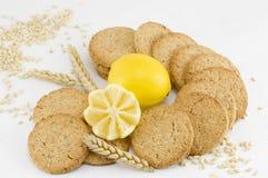 Väsentliga kex och dekorerad citron på vit bakgrund Royaltyfri Fotografi