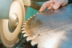 Vässa cirkelsågen, vässar arbetaren ett cirkelsågblad Arkivfoton