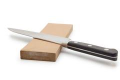 Vässa en kniv på en waterstone. Arkivbild
