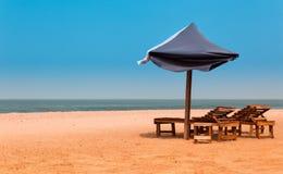 Västafrika Gambia - stolar och paraplyer på ett paradis sätter på land Arkivbild