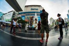 Västerlänningturister tar bilder av buddister som ber, Bangkok Arkivbilder