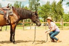 Västra cowgirlkvinna med hästen En cyklist- eller cyklistridning längs en konkret cykelbana Arkivfoton