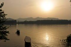 västra dimmig solnedgång för lake Arkivbild