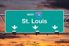 Västra huvudvägtecken för St Louis Interstate 70 med soluppgånghimmel Arkivfoto