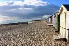 Västra Mersea strand med strandkojor och den mörka orosmolnet royaltyfri bild